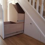 White banisters on under stair storage space on wooden flooring
