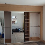 Mirrored wardrobes with doors open.