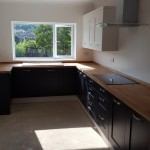 Bespoke kitchen with black cabinets and wooden hardtop