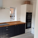 New kitchen installation with black cabinets and wooden counter, and fitted oven