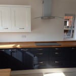 Kitchen installed; white hanging cupboards, black cabinets and wooden top finish.